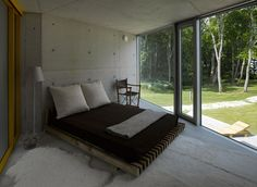 Smart Modern Home Ideas for a Seaside Residence: Small Bedroom In The Villa Lokaator With Wooden Bed And Dark Mattress On The Concrete Floor...