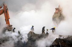 Firefighters make their way over the ruins of the World Trade Center through clouds of smoke as work continues at ground zero Thursday, Oct. 11, 2001, in New York, one month after the terrorist attacks on the Trade Center. (AP Photo/Stan Honda)
