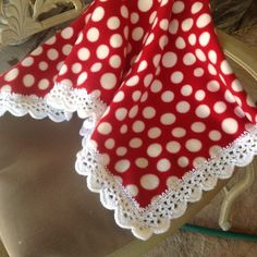 Red fleece baby blanket with white poka dots and a crocheted white edging.