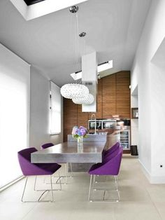 The kitchen island is a custom made concrete block. The concrete sink, which sits on a walnut base, goes on and continues as a big floating table. The coldness of this material is softened by Ligne Roset Papillon chairs and Foscarini Caboche chandeliers.