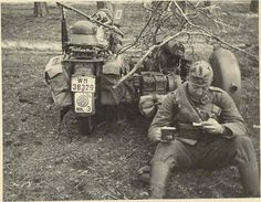 A soldier has time to relax with a cup of coffee next to his Zundap KS 750 and side car.