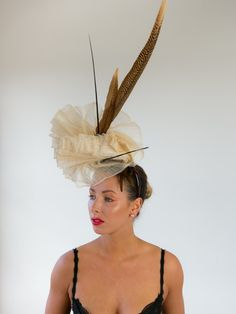 CHAMPAGNE TIFFANY | Hat/Fascinator for Caulfield Cup | FORD MILLINERY  $420  Hand-pleated vanilla sinamay, sculpted into one continuous double-fan that claims height and delicately touches the face. One ostrich quill spine orbits the centre, as the other stands tall fore contrast. Two glorious golden tail pheasant feathers (70-80cm) add even more height. Elegant, refined, and naturally glamourous. Fascinators, Headpieces, Caulfield Cup, Spring Racing Carnival, Pheasant Feathers, Millinery Hats, Quill, Sculpting, Tiffany