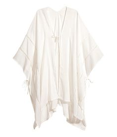 Powder pink. Poncho in airy, woven viscose fabric with lace insert details. Ties at front and at sides.