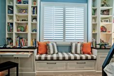 A window seat and built-in white shelving pop against blue walls in this fab kid's room. Gray and white striped fabric for pillows and cushions is combined with orange to keep the space feeling fun and youthful.