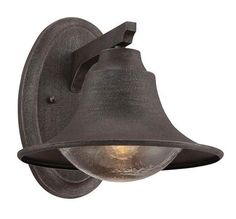 With its rust-tone finish, this outdoor sconce has a perfectly weathered look. The graceful bell-shaped shade allows a seeded-glass globe to peek out and light your front stoop. About $118; Shades of Light.