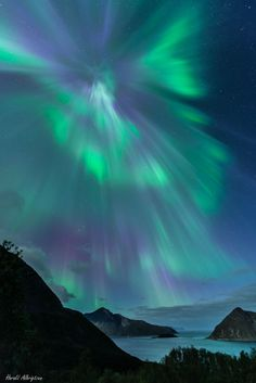 Auroral Corona over Norway : Higher than the highest mountain lies the realm of the aurora. Auroras rarely reach below 60 kilometers, and can range up to 1000 kilometers. Aurora light results from energetic electrons and protons striking atoms and molecules in the Earths atmosphere. Somewhat uncommon, an auroral corona appears as a center point for a surrounding display and may occur when an aurora develops directly overhead, or when auroral rays are pointed nearly toward the observer. ...