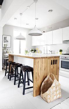 Unelmien hirsitalo Turussa | Suuri, puupintainen saareke tuo lämpöä valkoiseen keittiöön. Keittiössä ei ole lainkaan perinteistä, korkeaa jääkaappia, vaan saarekkeen alta löytyy laatikkojääkaappi.