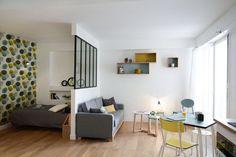 Une verrière d'intérieur type atelier permet de séparer le coin nuit du salon dans un studio.