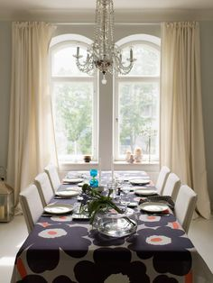 Marimekko's signature flower print table cloth adds a pop to a neutral dining room. Natural light floods the minimalist space (at least in the summertime when there can be daylight for 18 hours) which, is used often for entertaining friends and family.