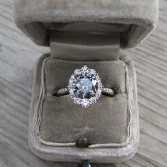grey moissanite halo engagement ring with diamonds in 14k gold modeled in engagement ring box
