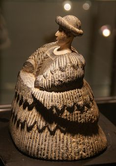 """Bactrian statue of woman from an auction at Christie's. Bactrian female figure with a huge pleated dress. It comes from Bactria-Margiana and is dated Late 3rd-Early 2nd Millennium B.C. It is 7 1/4 inches high. The """"shelf"""" at the west was for the now missing, separately made forearms. The dress, which is similar to some on some Sumerian figures, is made of chlorite and the face is white limestone. There is a closely related work in the Louvre."""