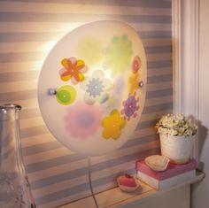 """Schlummerlicht """"Sommerblumen"""" - Diese Lampe ist perfekt für alle Blumen-Elfen, denn hier schimmern und leuchten ganz verschiedene Blüten. Wenn das Licht an ist, entfaltet die Lampe ihre ganze Blütenpracht, denn einige Blumen verstecken sich hinter der weißen Folie. (Artikelnummer 7477)"""
