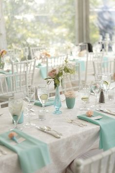 Ivory linens, mint napkins, minty vases, coral/peach flowers.