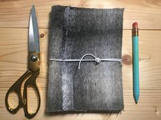 A faux fur handmade and hand bound book that can be used as a journal, sketchbook, notebook or whatever your heart desires.  It is a fluffy faux fur handmade book with a long stitch spine. It has a white elasticated wrap. This stitch is created with a light brown gradient coloured string