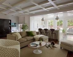 Chic living room features a coffered ceiling over a camel colored velvet sofa with chaise lounge lined with an emerald green velvet pillow as well as a cream and beige fretwork pattern chair facing an oval wood top Saarinen Coffee Table top a bound sisal rug.