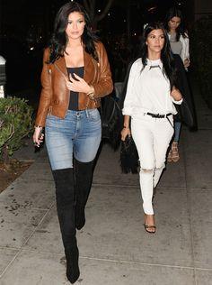 Look de Kylie Jenner com calça jeans, regata preta, bota over the knee e jaqueta biker marrom.
