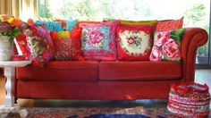 Bright red sofa makes a bold statement with colorful pillows, flowers, and a woven fabric basket.