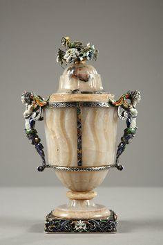 Un vase en agate décoré de longs canaux torses et godrons saillants, avec monture en émail décorée d'entrelacs et volutes fleuries. Deux jeunes femmes en buste terminé en rinceau...