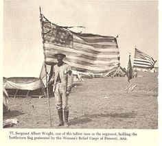 Rough Rider holding battle torn flag.