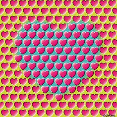 E-Motion (Peripheral drift illusion). As you sweep your gaze around the picture, the small red hearts appear to move diagonally in two opposite directions, while the large blue heart seem to pulsate slightly. The shaded tones and the contrasting black and white edges of the small hearts induce a shifting in the retinal image when your eyes move, activating motion-sensitive neurons in your brain. This activation is incorrectly translated as a real motion. © GIanni A. Sarcone…