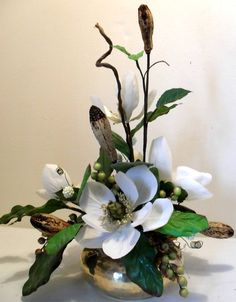 Magnolia & Mahogany Pod Arrangement Lovely vintage brass container filled with beautiful silk magnolias and natural dried pods and green berries, accented with silk magnolia leaves. 20-inches high,19-inches wide and 12-inches deep. All hand wrapped here at our own floral department. SOLD