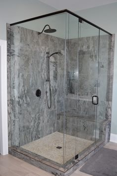 Master bathroom with grey shaker vanity, porcelain tile, pebble shower floor, oil rubbed bronze fixtures, Glass shower with bench seat and niche, freestanding soaker tub and shutter window coverings.