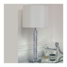 Faceted crystal table lamp with a chrome effect plate base complemented with a simple, silk effect shade