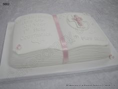 Open book shaped communion cake with sugar cross mounted on a plaque trimmed in pink