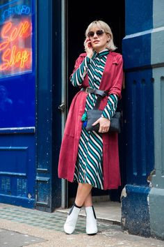 A red trench is worn belted over a striped button down dress, paired with white booties