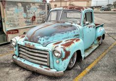 1953 GMC pickup truck with an amazing blue patina'd original paint job with a white interior and cool hooded headlight trim rings all slammed over five spoke wheels.