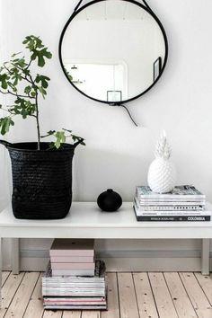 Miroir couloir. Quelques magazines sont poses sur la table.