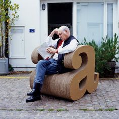 """a"" CHAIR MADE OUT OF CARDBOARD..SEATED IS GRAPHIC DESIGNER: ALAN FLETCHER (09-27-1931 til 09-21-2006, Age: 74)"