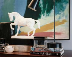 Eclectic Midcentury Details: A white horse statue and a black task lamp on a wooden console.