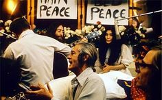 """Lennon and Ono used their honeymoon as """"Bed-in"""" March 1969.  At a second Bed-In three months later at the Queen Elizabeth Hotel in Montreal. Lennon wrote and recorded """"Give Peace a Chance"""".  Lennon and Ono sit in front of flowers and placards bearing the word """"peace.""""Lennon is only partly visible, and he holds an acoustic guitar. Ono wears a white dress."""