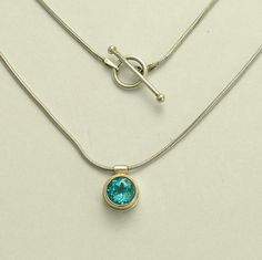 Island Blue  ~~~~~~~~~~~~~~~~~  The sterling silver necklace has a 9K yellow gold and sterling silver pendant with a blue topaz stone. (N0440X)