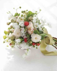 """When designing your posy, apply the gardener's adage """"If it grows together, it goes together."""" This sweet-as-cobbler clutch pairs flowering strawberries and sweet peas with blush and white Fair Bianca roses, starlike tweedia, and Canterbury bells. The mix of blooms and fruit gives off a delicate fragrance that will waft down the aisle, just like its fluttery green silk-satin ribbon.75mm Mokuba New York ribbon in color #38 (212-869-8900)."""