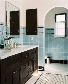 Vintage updated bath bathroom blue square ceramic tile black liner double vanity arch entry marble mosaic basketweave rug