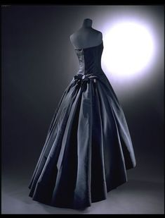 Evening dress | Christian Dior (French, 1905-1957) | Paris, 1955-1956 | Silk faille, boned, and tulle net | This silk evening dress is one of Dior's Y-line designs. The strapless 'princess' style gown is a sculptural masterpiece. Haute couture designers enjoyed making two dresses in one. Here the front skirt is short, reaching lower calf level. At the back the skirt is long and forms an impressive train that sweeps the floor | VA Museum, London