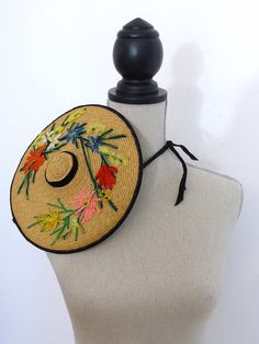 Jaunty 1950s mini straw hat with a pretty floral embroidery. This would look wonderful at a wedding or garden party.  Brand:  A la Niçoise The original label includes the boutique address: 1 Rue Saint-Françoise de Paule, Nice. Sadly it no longer exists.  Very Audrey Hepburn!