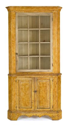 "Realized Price: $5103   Pennsylvania painted two-part corner cupboard, early 19th c., the ogee cornice over a glazed door resting on a base with raised panel doors, above a scalloped apron supported by bracket feet, 87 1/4"" h., 41 1/2"" w."