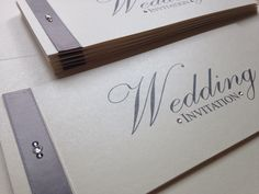 Stylish and elegant cheque book wedding invitation. Ivory pearl combined with charcoal grey satin ribbon, with black diamond and clear crystals.