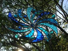 Different types of Blue pieces of glass swirling out from a center nugget. This piece is made to free hang so it can spin and twirl around.
