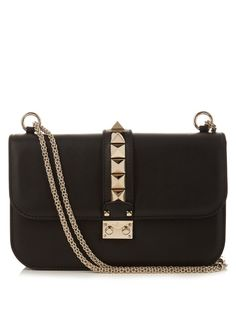 Valentino's black calf-leather Lock bag is a signifier of modern luxury. The compact shape is decorated with gold-tone platinum-finish hardware, Rockstuds, and topped with a chain shoulder strap that can be doubled to create a shorter length. Make it a new-season essential and carry day and night.