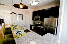 Premium open kitchen with all new stainless steel appliances: microwave, refrigerator, oven, dishwasher. Also includes granite countertop and tiled backsplash.