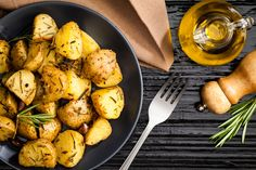 Top view of roasted potatoes served in a gray plate on black table. The plate is located at the left of the frame with a fork beside it while a olive oil bottle and a pepper mill are at the top-right. A brown fabric napkin is at the top. DSRL studio photo taken with Canon EOS 5D Mk II and Canon EF 100mm f/2.8L Macro IS USM