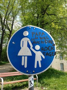 """As is common, the adult has been carefully altered to be identifiable as female because the sign is in reference to caretaking kids.  Someone in Goettigen found this as annoying as we do, however, and scribbled upon the sign: ""Daddy, I also want to wear a skirt.""  What a fabulous way to fight back against rigid gender rules."""