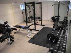 fully equipped basement gym with lat pulldown, rack, benches and dumbbells