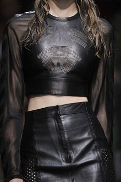 Black perforated leather skirt + crop top with sheer sleeves; fashion details.