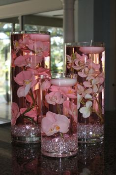 Pink-tinted water with jewels and orchids with a floating candle! The different sizes help to add a bit of flare.