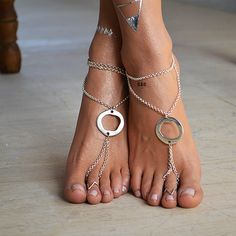 A pair of handcrafted barefoot sandals, with silver chain.   The sandals have a silver metallic flat ring in the center that looks very attractive. Silver chain surrounds the leg in two positions, one chain on the top of the sandal and one that it tied to the ring.  ➡The silver chain is very shiny and glossy, just like the charm.  The closure is adjustable. It has a silver clasp at the back.  Comfortable fit for all foot sizes.  You can wear them barefoot in the beach or with your favori...